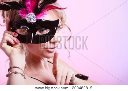 Party time holidays people and celebration concept. Woman middle aged blonde female holds carnival mask. Lady wearing elegant black dress