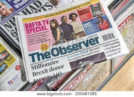 LONDON ENGLAND - MAY 14 2017 : The Observer newspaper laying on different newspapers. The Observer is a British newspaper published on Sundays.