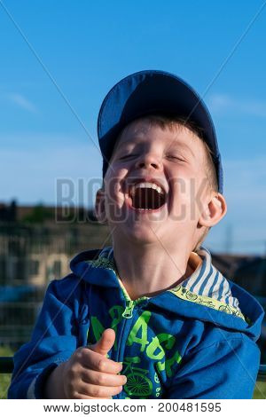 A fun happy little boy laughs very much. The boy closed his eyes in pleasure and opened your mouth wide while laughing. In the background the blue sky and building.
