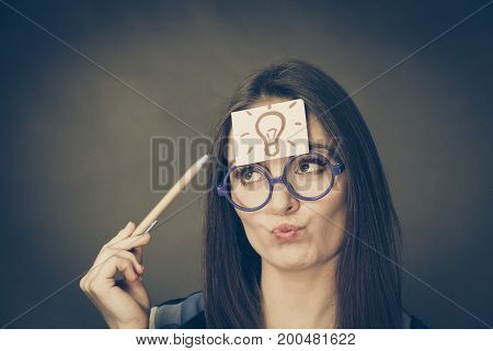 Woman confused thinking seeks a solution paper card with light idea bulb on her head. Student girl looking for new ideas. Eureka creativity concept