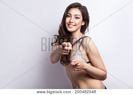Hey you! Come to my. Playfully young model pointing finger and looking at camera with toothy smile. Isolated on gray background. Studio shot