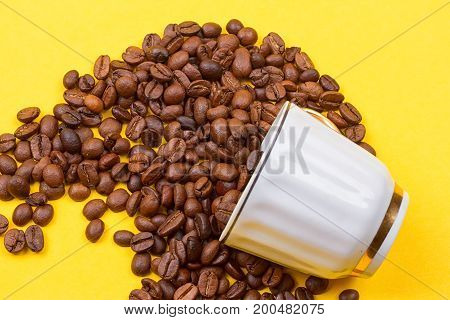 Coffee cup full of coffee beans on the yellow background