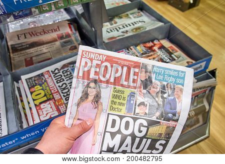 LONDON ENGLAND - MAY 14 2017 : A hand holding The Sunday people newspaper. The Sunday People is one of Britain's oldest Sunday newspapers