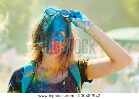 Portrait of a beautiful girl full of colored powder all over the body