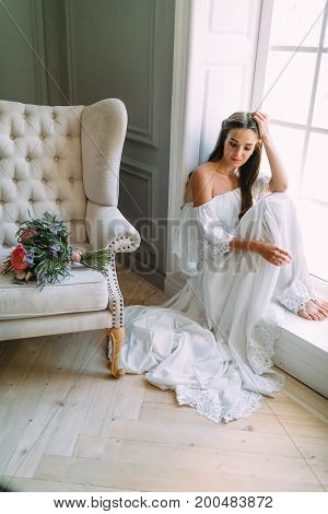 Woman By The Window. Bride Waits For The Groom. A Bridal Bouquet Lies On The Sofa.