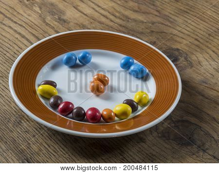 Smile From Colorfull Candy Bonbon White Brown Plate On Wooden Desk