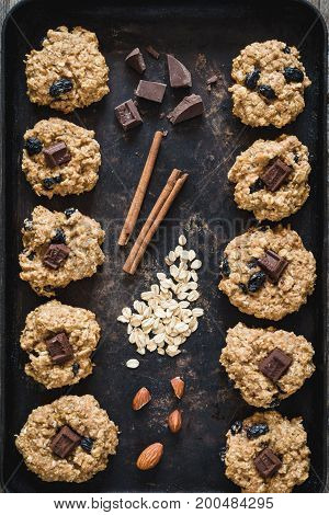 Top view of freshly baked oatmeal raisin cookies with dark chocolate, cinnamon and nuts on old rusty cookies sheet.