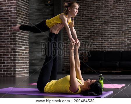 Young Caucasian mother and happy school-age daughter wearing the same sportswear doing partner yoga exercise in modern fitness studio.