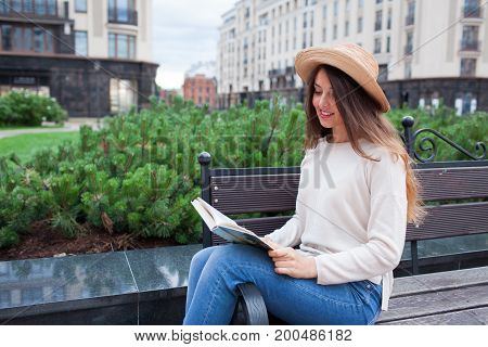 A Young Beautiful Woman In An Elegant Hat Sits On A Bench In A New Residential Neighborhood And Read