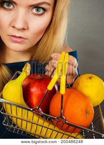 Buying healthy food vegetarian gluten free vegan products. Unhappy woman holding shopping cart with fruits inside