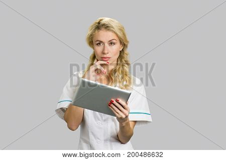 Portrait of young nurse with digital tablet. Thoughtful young female doctor or nurse holding computer tablet and having an idea, grey background.