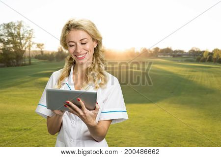 Beautiful nurse with pc tablet outdoor. Smiling young female doctor using digital tablet on nature background. Positive emotions with electronic technology outdoor.