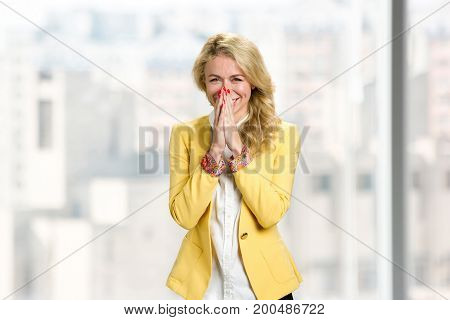 Happy young lady in formal wear. Cheerful young woman clasped her hands near mouth. Facial expressions of happiness.