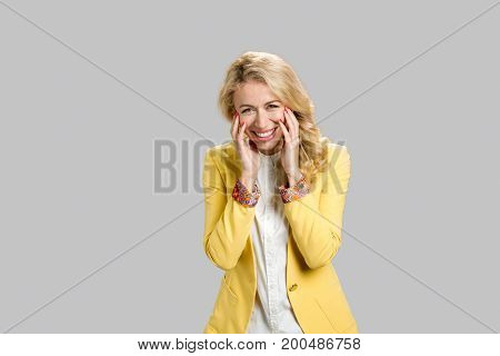 Young lady laughing on grey. Cheerful beautiful business woman smiling holding her hands near cheeks over grey background.