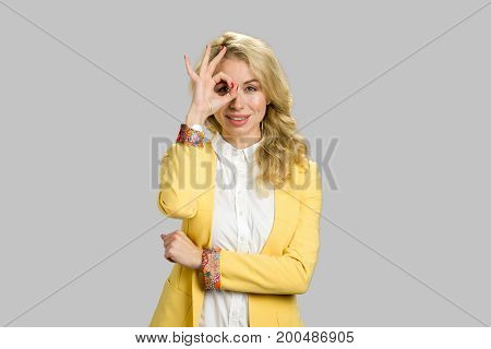 Attractive young business woman showing OK gesture. Portrait of an attractive young woman showing OK sign over grey background.