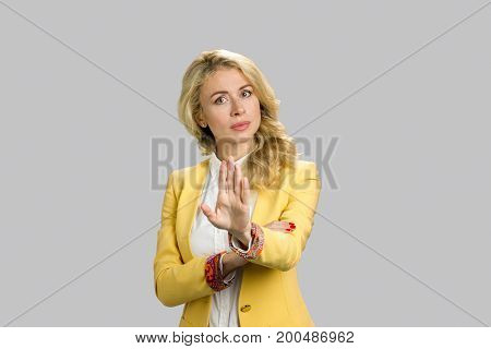 Serious young woman gesturing stop. Young business woman making stop sign on grey background.