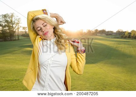 Beautiful young woman stretching outdoor. Attractive tired fatigued woman stretching extending arms, back, shoulders on naturer background.