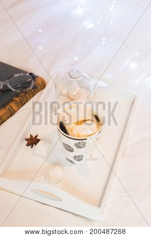 Breakfast in bed - tray with warm drink and marshmallows, cozy hygge home style