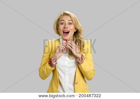 Portrait of excited happy shocked woman. Beautiful european surprised woman amazed in shock isolated on grey background.