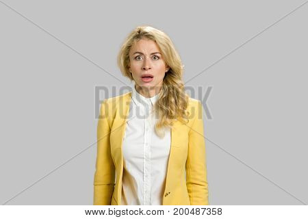 Shocked and scared young business woman. Scared and shocked young blond woman standing in full disbelief on grey background.