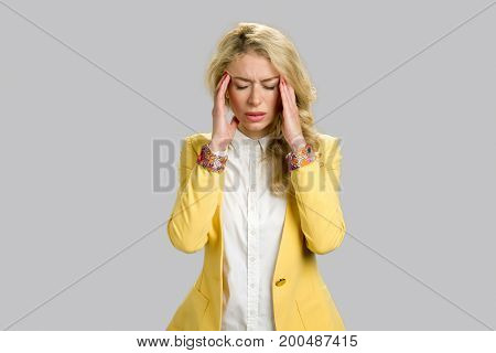 Portrait of beautiful young lady with headache. Attractive girl in formal wear having a headache against a grey background.