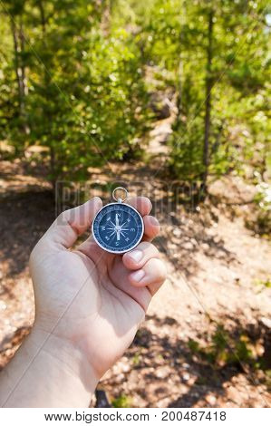 Hand holding the compass. Hike travel concept.