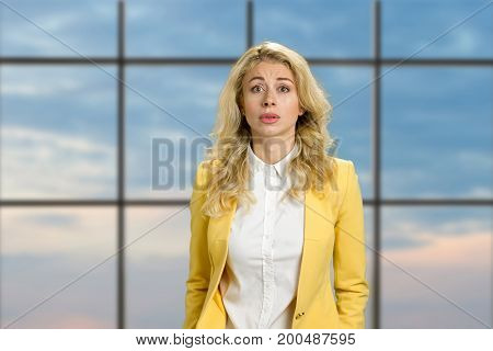 Portrait of disappointed young woman. Beautiful upset blonde looking confused on blue sky office window background. Human facial expressions.