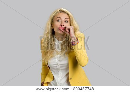 Blonde young woman making funny lips. Young business woman making funny grimace with her lips standing on grey background.
