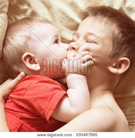 Two brothers play and hug in bed before bedtime
