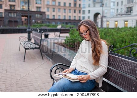 Young Beautiful Girl With Glasses Long Brown Hair Sitting On A Bench With A Book. She Left The House