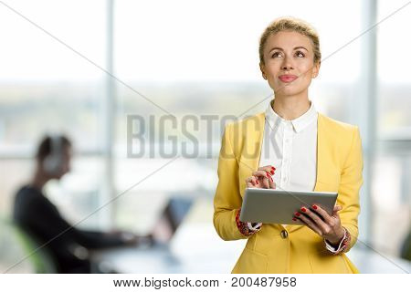 Thoughtful business lady with digital tablet. Attractive business woman using a digital tablet while standing in front of windows in an office building and thinking looking upwards.