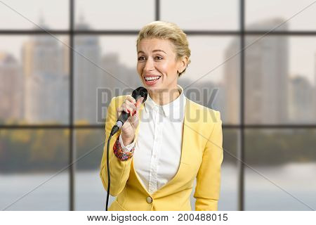 Pretty young business woman giving a presentation. Public speaking young business woman, business center window background.
