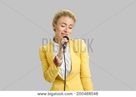 Beautiful young lady singing karaoke. Charming young woman singing into a microphone karaoke showing expressions and feelings isolated on grey background.
