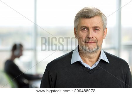 Mature man on office background. Portrait of senior man in formal wear with silver hair. European mature man in casual wear.