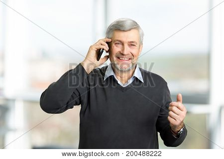 Cheerful mature man with phone. A horizontal portrait of mature man with grey hair and wrinkles talking on smartphone, blurred background.