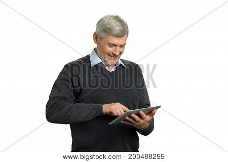 Mature man using computer tablet. Smiling elderly man working on digital pc tablet with index finger. Positive senior man with pc tablet on white background.