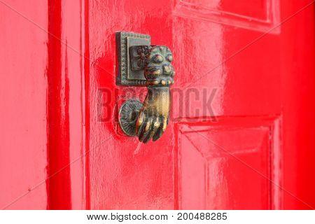 Red lacquered door with doorknocker Metal arm of woman