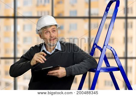 Mature foreman looking upwards. Elderly engineer checking the construction with clipboard, ladder, blurred background.