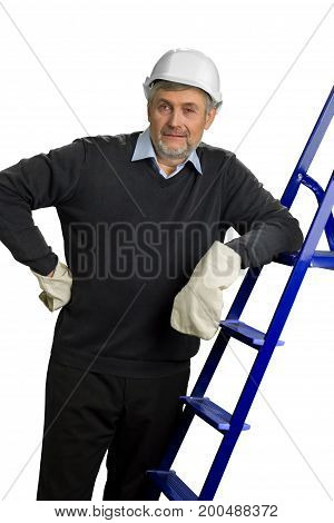 Contractor in helmet and gloves leaning on ladder. Mature construction supervisor in white safety helmet and gloves leaning on ladder, white background.