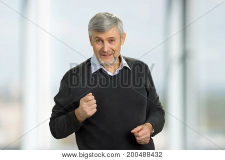 Senior man putting his fist up. A handsome mature man showing his fist while being angry and irritated.