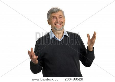 Portrait of an excited mature man standing with raised hands and looking upwards on white background.