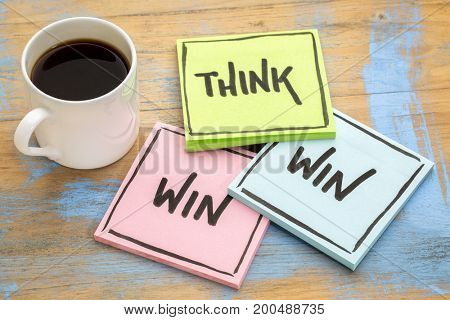 Think win-win concept  - handwriting on sticky notes against grunge wood board with a cup of coffee