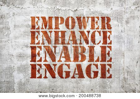 empower, engage, enable, and enhance inspirational leadership concept - graffiti sign on stucco wall