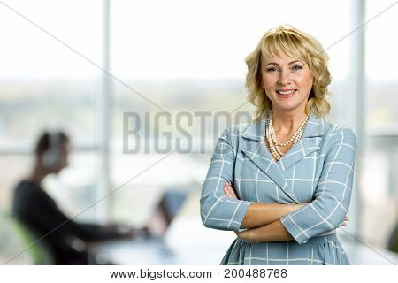Mature woman with crossed arms. Portrait of cheerful white-skin woman with crossed arms on office background.
