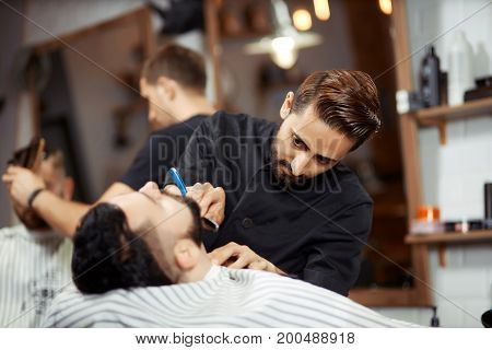 Handsome stylish shaving client in chair using sharp razor and working in barbershop.