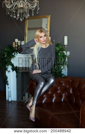 Attractive Blond Girl In Beautiful High-heeled Shoes And Grey Sweeter And Trousers Sitting On The Be