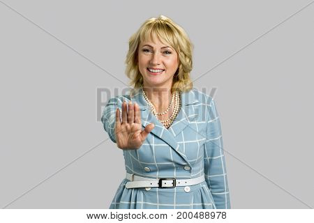 Smiling elegant woman making gesture stop. Joyful mature businesswoman gesturing stop sign while standing isolated on grey background.