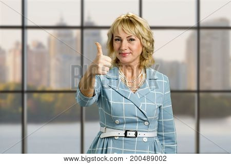 Elegant mature woman raised thumb up. Smiling white-skin lady raised her thumb up while standing on office window background close up.