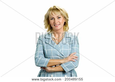 Elegant mature woman crossed arms. Smiling white-skin woman crossed arms standing on white background, front view.