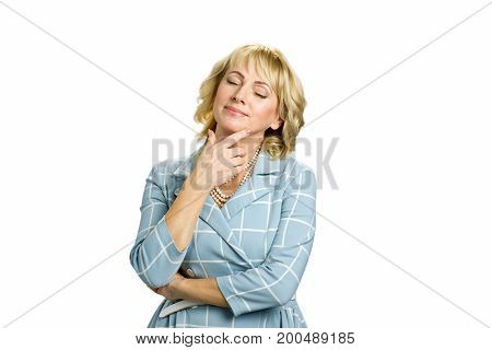 Relaxing woman on white background. Mature woman closed eyes and enjoy silence. Senior woman closed her eyes touching chin standing on white background.
